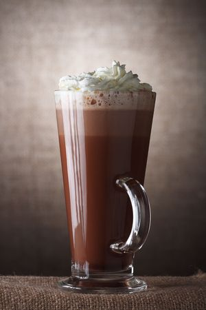 cappuchino: Hot Chocolate with cream in Tall Glass on brown rustic background