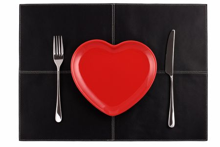place mat: empty red heart plates with a knife and fork on a black leather place mat Stock Photo