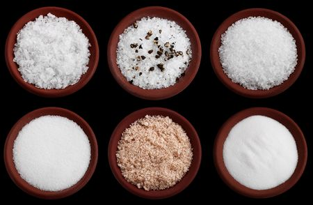 coarse: six terracotta plates with different salt - flakes sea salt, coarse sea salt with crashed black pepper, coarse sea salt, fine sea salt, smoked flaky sea salt, table salt, Isolated on black