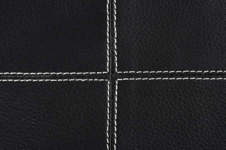 stitched: black leather background stitched up by white thread