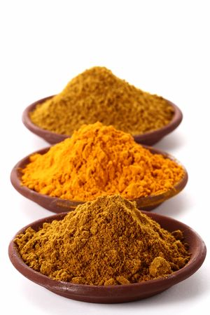 piles of bright Curry Powder and tumeric in teracotta dish on white, shallow DOF, focus on the first one.
