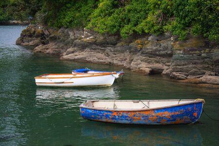 skiff: old cog fishing boats on the sea, white blue and orange, Cornwell, England Stock Photo