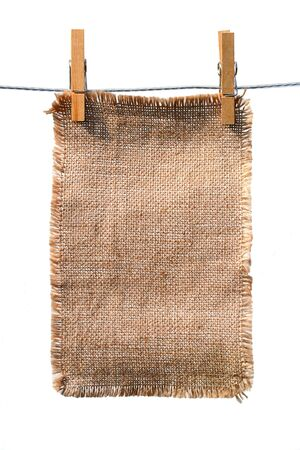 lacerate: burlap canvas with lacerate edges hanging with wooden pegs, isolated on white Stock Photo