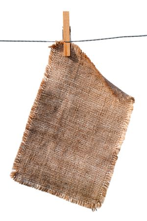 lacerate: burlap canvas with lacerate edges hanging with wooden peg, isolated on white Stock Photo