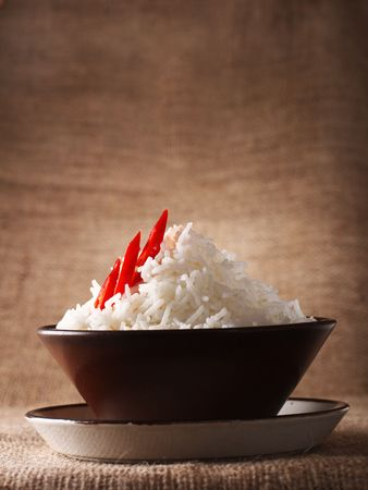 basmati: rice bowl with fresh chillies on brown rustic background, Low Key Lighting Technique, Shallow DOF
