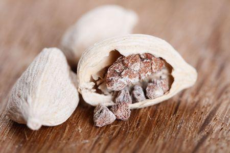 cardamum: white cardamom pods on old wood, one opened, super macro, shallow DOF
