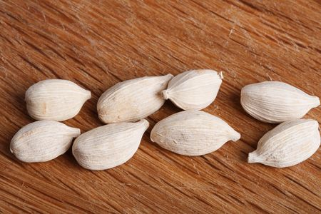 cardamum: eight white cardamom pods on old wood