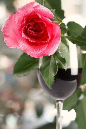 redwine: red rose on red wine glass, bright background, shallow DOF