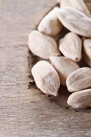 cardamum: white cardamom pods on old wood, macro, shallow DOF Stock Photo