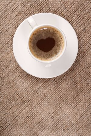 coffee sack: Cup of black coffee on hessian background,