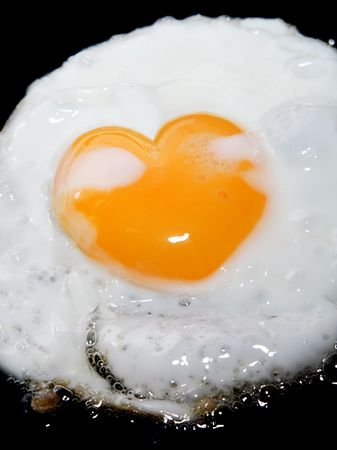 cooking frying egg with heart shape yolk on black photo