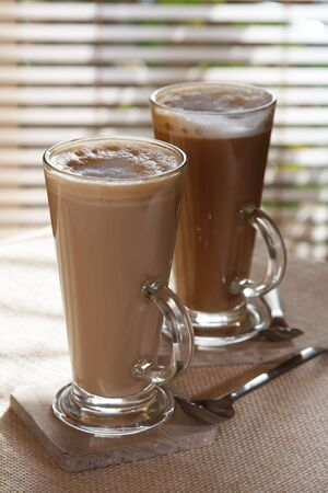 coffee latte macchiato or hot chocolate in tall glasses on window background, shallow DOF photo