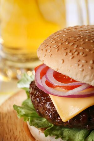burger on bun: classic cheeseburger with beer on background, shallow DOF