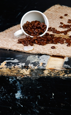 overturned: overturned coffee cup with beans on old black grunge table, shallow DOF