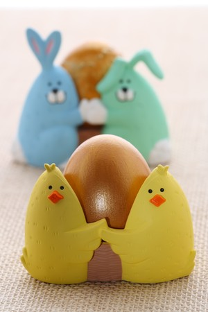 Easter egg in funny chick eggcup, on rustic background, shallow DOF photo