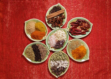 black peppercorn: various Spices in seven leaf shape plates on glitter red backdrop -  Gloves, Cinnamon, Anis, Chillies, Curry, Green White and Black Cardamom, Coriander seeds and Black peppercorn, Ginger Garam masala and Tikka masala powders, Black and Himalayan salt, Oni