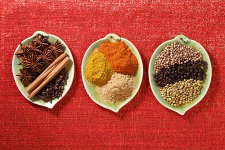 peppercorn: various Spices in three leaf shape plates on glitter red backdrop -  Gloves, Cinnamon, Anis, Coriander seeds and Black peppercorn, Ginger Garam masala and Tikka masala powders