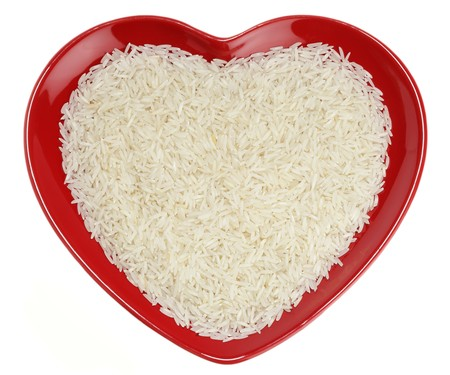 Traditionally Indian basmati Rice in red heart shaped plate, isolated over white