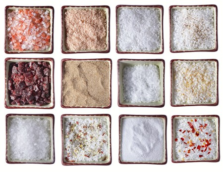 twelve types of Sea SALT in square bowls, over white