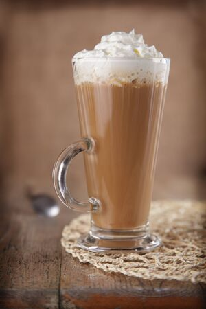 Coffee Latte with whipped cream in rustic style, shallow DOF, rough vignette for style
