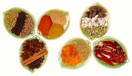 garam: various Spices in six leaf shape plates isolated on  white background - Gloves, Cinnamon, Anis, Chillies, Curry, Green White and Black Cardamom, Coriander seeds and Black peppercorn, Ginger Garam masala and Tikka masala powders Stock Photo