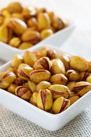 Roasted salted pistachios in a square bowls, soft focus