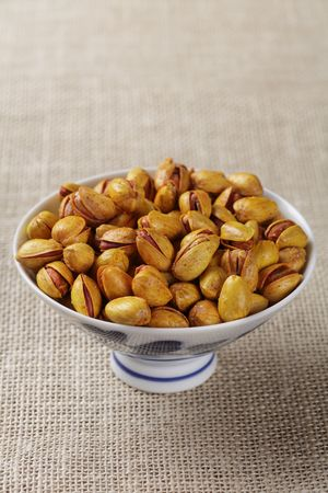 Roasted salted pistachios in an elegant bowl, shallow DOF photo