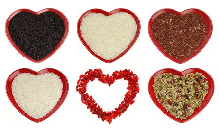 different sort of rice and goji berryes heart shape, bright red color, over white  Stock Photo