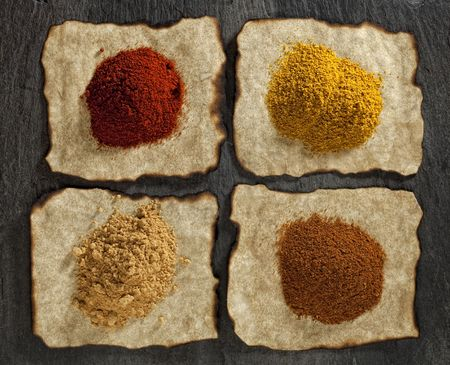 paprika, ginger, curry, tikka masala powders on old paper with burnt edges ,  black stone backdrop photo