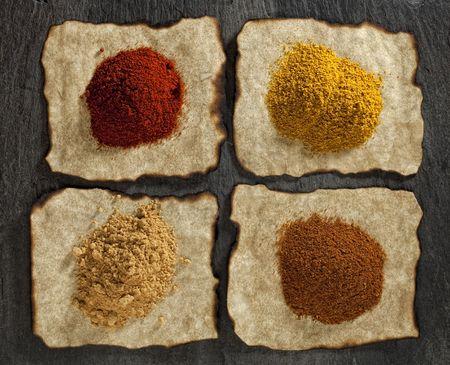 masala: piment�n, jengibre, curry, Tikka Masala polvos en papel viejo con los bordes quemados, negro tel�n de fondo de piedra Foto de archivo