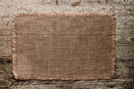 lacerate: burlap canvas with lacerate edges on old grunge wooden background Stock Photo