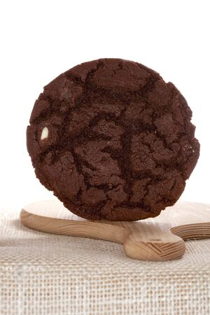 chocolaty: very chocolaty american style cookie free standing on wooden board, white backdrop, shallow DOF