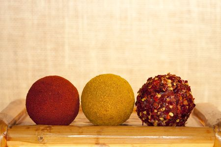 paprika, hot curry powder and crushed chillies in balls shape on old bamboo table, shallow DOF photo