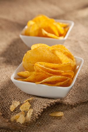 gease: potato crisps in two white bowls on hessian background, shallow DOF