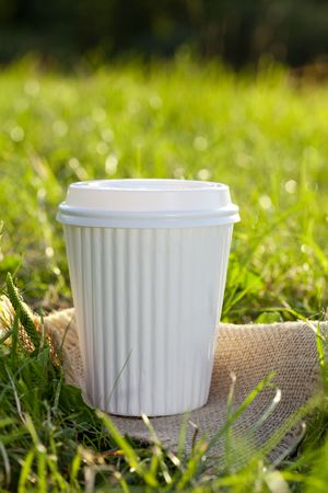 white take out coffee cup in the grass, shallow DOF photo