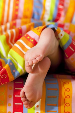 girl lying studio: toddlers girl  feet in a bed under the morning sun, shallow DOF Stock Photo