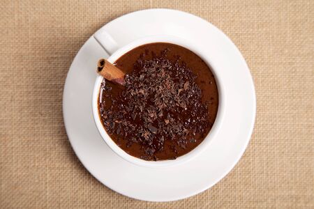 hot chocolate in white mug with cinnamon stick, saucer and 100 percent chocolate flakes, on jute backdrop, top view photo