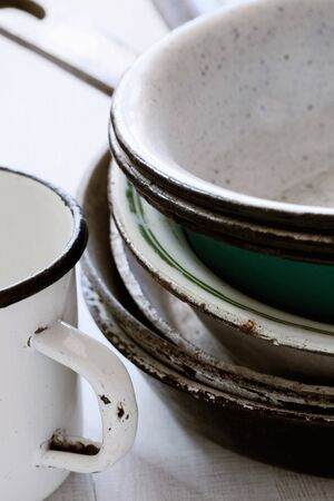 very old enamelled dishware, assorted enameled plates pans  and a mug , shallow DOF photo