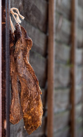cured: Biltong - dry cured meat on a wooden fence