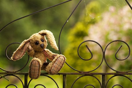 soft toy: small rabbit soft toy sitting in an iron fence, Authors work with property release Stock Photo