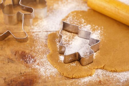 christmas gingerbread tree cookie cutter on dough with rolling pin, full frame photo