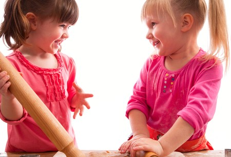 two little girls with rolling pins baking cookies, on white Stock Photo - 8139677