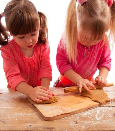 two busy little girls kneading and rolling gingerbread dough photo