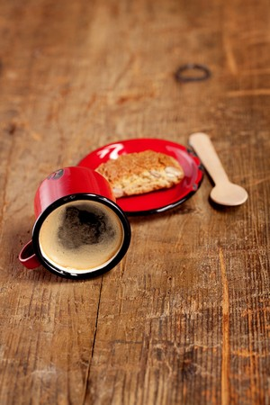 extremely  overturned espresso coffee in red enamel mug with saucer, wooden spoon and  Cantuccini Biscotti photo