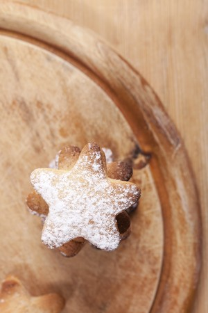 homemade gingerbread  star cookies stacked, on wood background photo