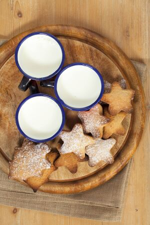 homemade gingerbread  star cookies with three kids milk on wooden table photo
