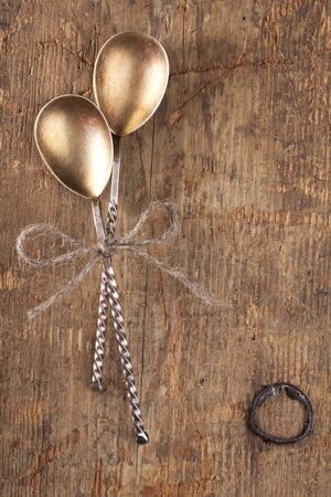 chabby: two retro desset spoons tied on old wooden table