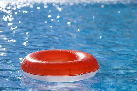floating  ring on blue water swimpool with waves reflecting in the summer sun photo