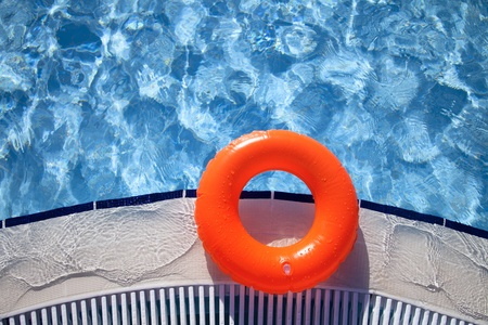 floating orange ring on edge of swimpool with waves reflecting in the summer sun Stock Photo