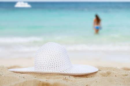sunbathe: sea, beach, white hat,  girl  and boat.  shallow dof